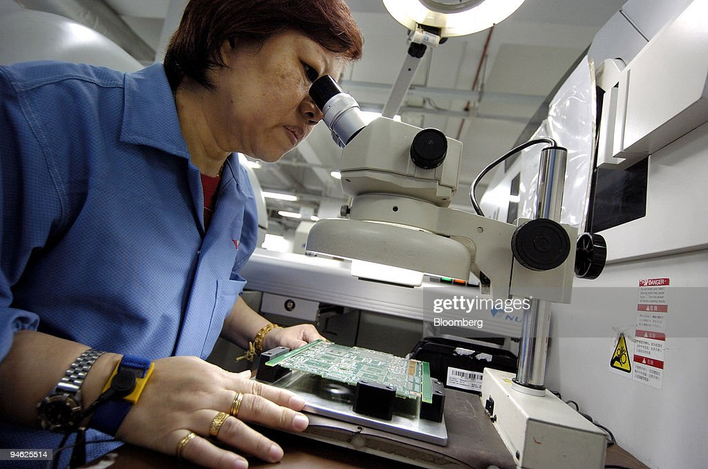 An assembly line worker inspects a circuit board at Venture Pictures ...