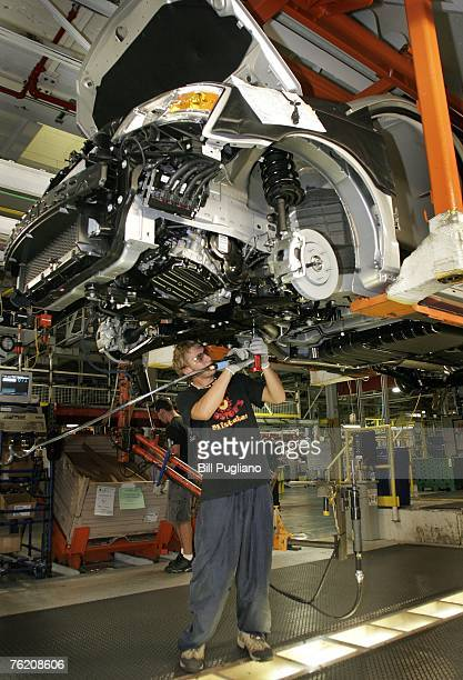 An assembly line worker installs front brake line brackets on new 2008 minivans the Chrysler Tow Country and the Dodge Caravan at the Windsor...