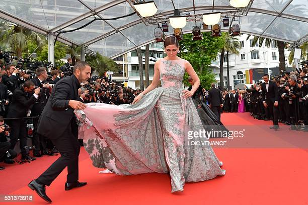 An assistant adjusts the dress of BritishThai actress Araya A Hargate as she arrives on May 14 2016 for the screening of the film 'The BFG' at the...