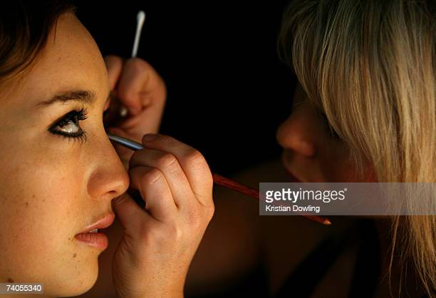 An assistant applies eye makeup to a model prior to the Women's Ready To Wear 7 Catwalk on day four of the Rosemount Australian Fashion Week...