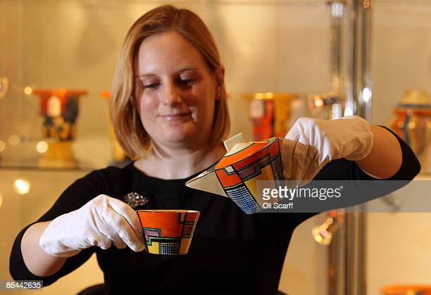 An assistant at Bonhams auction house uses a teapot by acclaimed designer Clarice Cliff ahead of an auction of 100 Clarice Cliff ceramics on March 16...