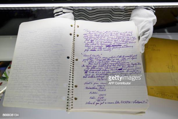 An assistant displays US singersongwriter Prince's handwritten prescript of Purple Rain during a press preview of the 'My Name Is Prince' exhibition...