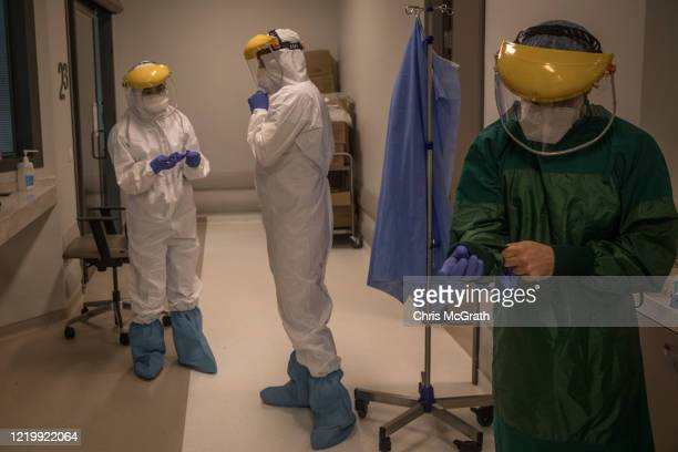 An assistant doctor and nurses get dressed in personal protective equipment before performing a procedure on a patient infected with the COVID19...