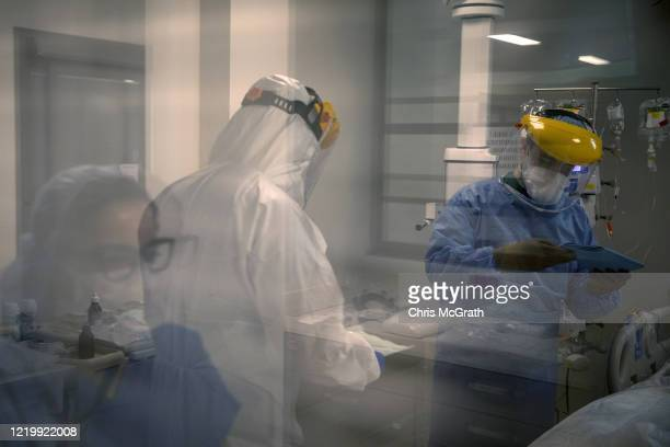 An assistant doctor and nurses prepare to perform a procedure on a patient infected with the COVID19 virus in the COVID19 dedicated ICU at the...