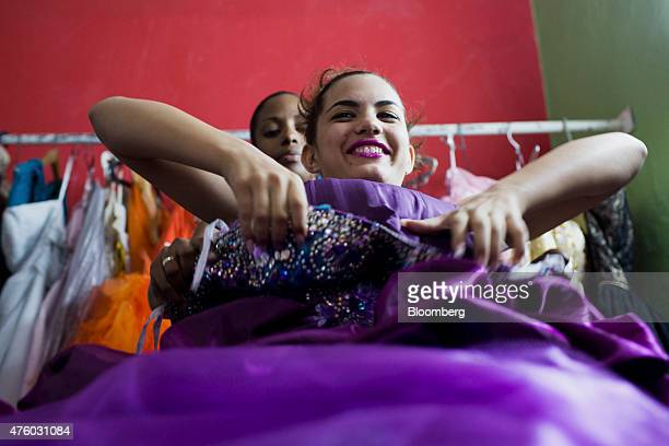 An assistant helps Liliana Cordero Perez try on a dress during a photo shoot ahead of her quinceanera celebration in Havana Cuba on Sunday March 2015...