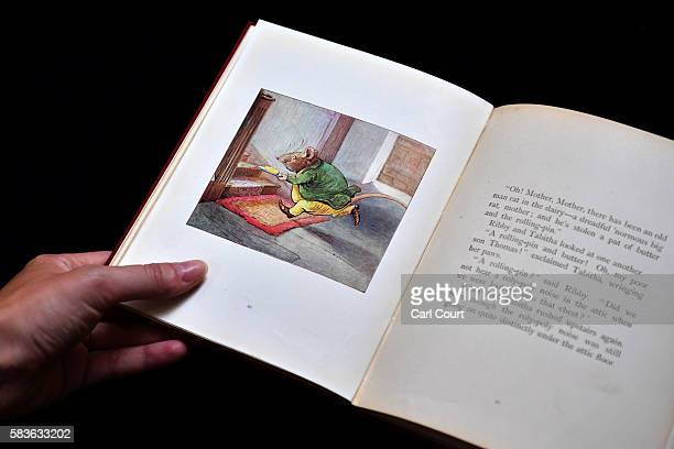 An assistant holds a first edition of The Roly-Poly Pudding by Beatrix Potter at Dreweatts and Bloomsbury Auctions on July 27, 2016 in London,...