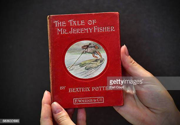 An assistant holds a first edition of The Tale of Mr Jeremy Fisher by Beatrix Potter at Dreweatts and Bloomsbury Auctions on July 27, 2016 in London,...