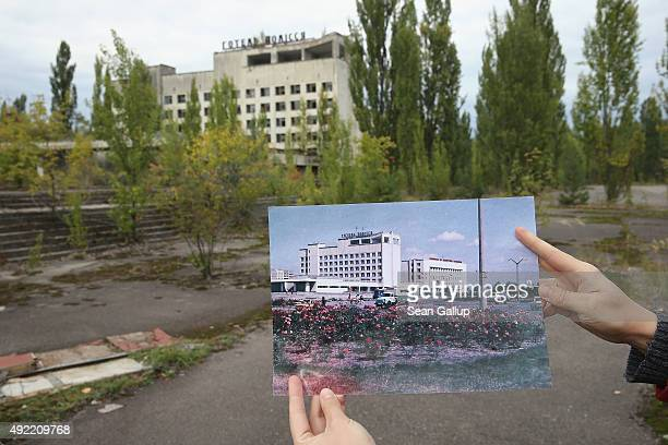 An assistant holds up a photo showing the city of Pripyat's main square and the Polissya hotel before 1986 at the same site that today is abandoned...