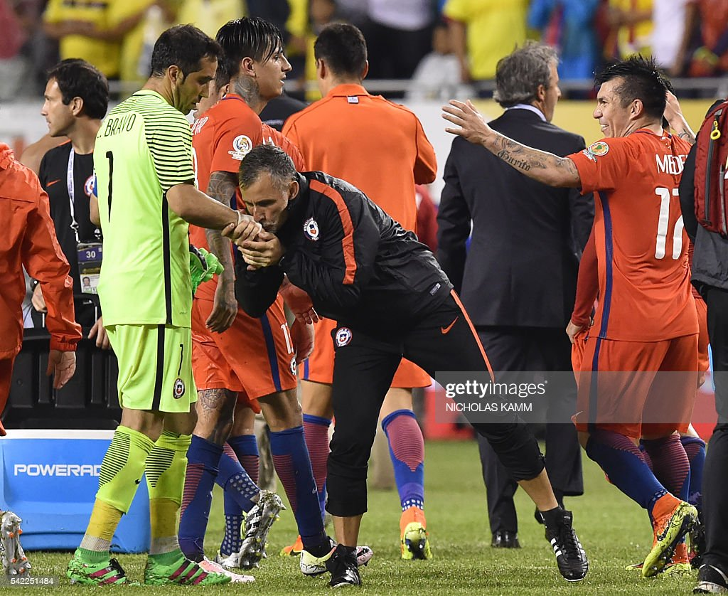 TOPSHOT - An assistant kisses the hand of Chile's goalkeeper Claudio Bravo (L) in the end of a Copa America Centenario semifinal football match against Colombia in Chicago, Illinois, United States, on June 22, 2016. / AFP / Nicholas Kamm