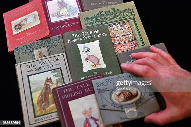 An assistant moves a book displayed with other Beatrix Potter novels at Dreweatts and Bloomsbury Auctions on July 27, 2016 in London, England....