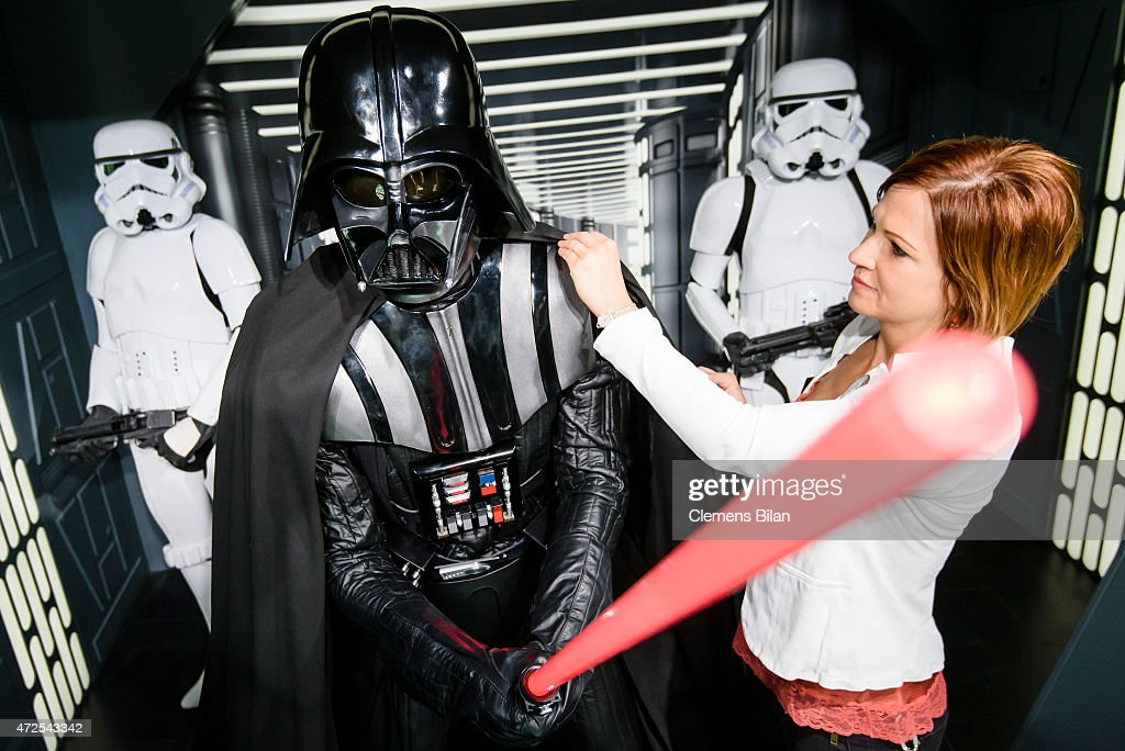 An assistant of the the exhibition poses with a wax figure of the Star Wars characters Darth Vader (C) and two Stormtroopers (L, R) that are displayed on the occasion of Madame Tussauds Berlin Presents New Star Wars Wax Figures at Madame Tussauds on May 8, 2015 in Berlin, Germany.