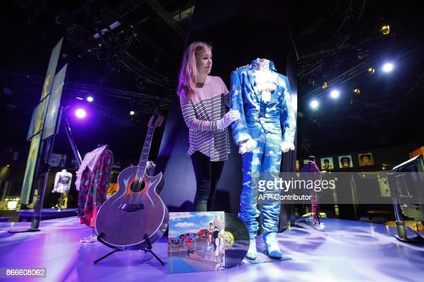 An assistant poses with a cloud outfit worn by US singersongwriter Prince on his Raspberry Beret music video during a press preview of the 'My Name...