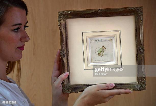 An assistant poses with an original watercolour study of Beatrix Potter's Miss Moppet's Mouse at Dreweatts and Bloomsbury Auctions on July 27 2016 in...