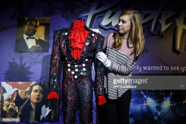 An assistant poses with an outfit worn by US singersongwriter Prince on his Purple Rain tour during a press preview of the 'My Name Is Prince'...