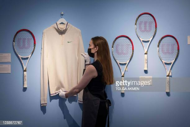 An assistant poses with Swiss tennis champion Roger Federer's cardigan and racket from Wimbledon 2012 and rackets from the Olympics 2012 during a...