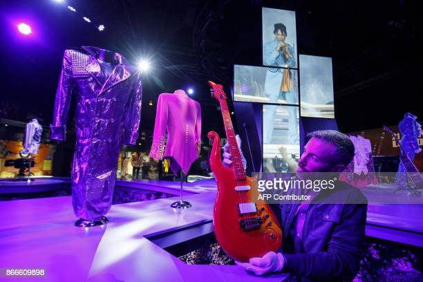 An assistant poses with US singersongwriter Prince's orange cloud guitar which was originally made for his Super Bowl performance during a press...