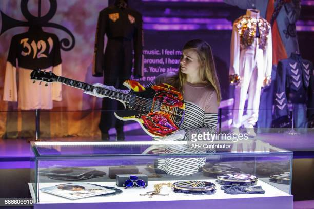 An assistant poses with US singersongwriter Prince's Vox guitar during a press preview of the 'My Name Is Prince' exhibition at the O2 Arena in...