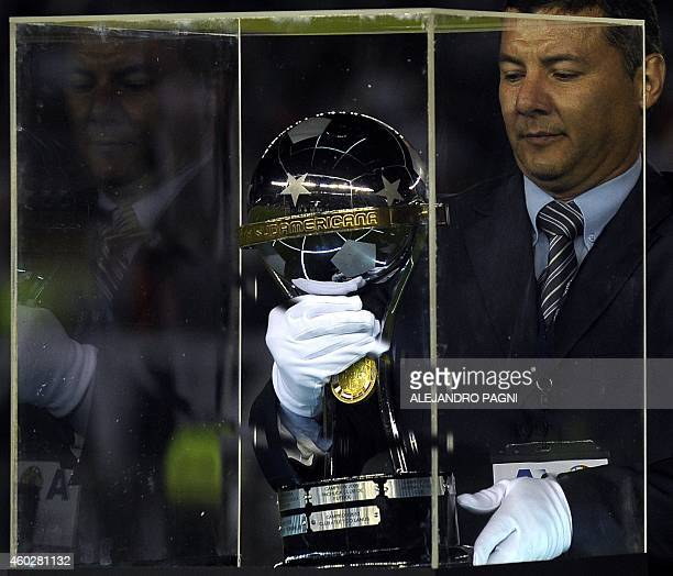 An assistant puts the trophy inside a glass case before the Copa Sudamericana 2014 final football match between Argentinian River Plate and Colombian...