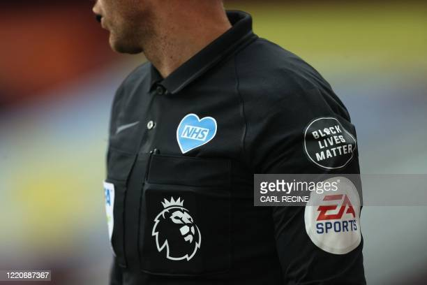 TOPSHOT An assistant referee wears a uniform bearing a heartshaped NHS logo and a Black Lives Matter badge during the English Premier League football...
