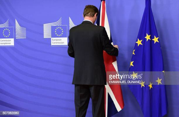 An assistant sets up a United Kingdom and a European Union flag prior to a meeting between the British prime minister and the European Commission...
