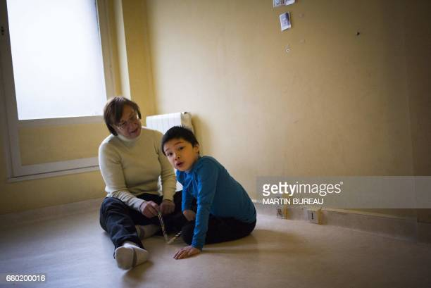 An assistant takes care of Jules a 8yearold autistic boy on March 24 2017 in Courbevoie northwest of Paris at the Lud'Eveil center for children with...