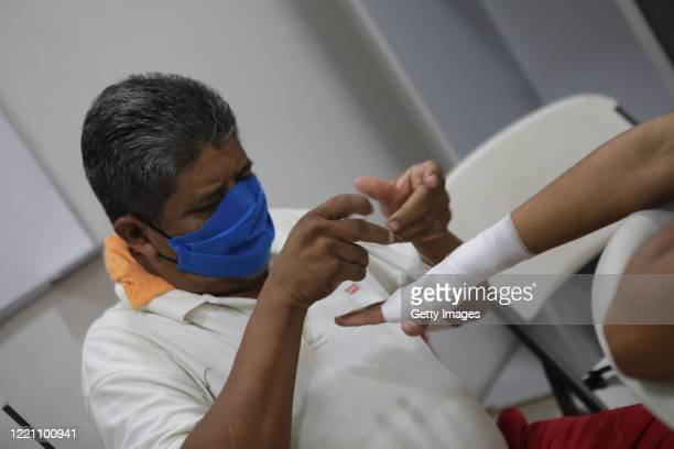 An assistant wearing a face mask wraps the hands of a boxers in the locker room at Alexis Arguello Sports Center on April 25 2020 in Managua...