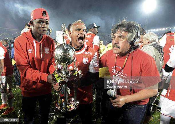 An assitant of Santa Fe celebrates with the trophy after a second leg final match between Santa Fe and Deportes Tolima as part of Liga Aguila II 2016...