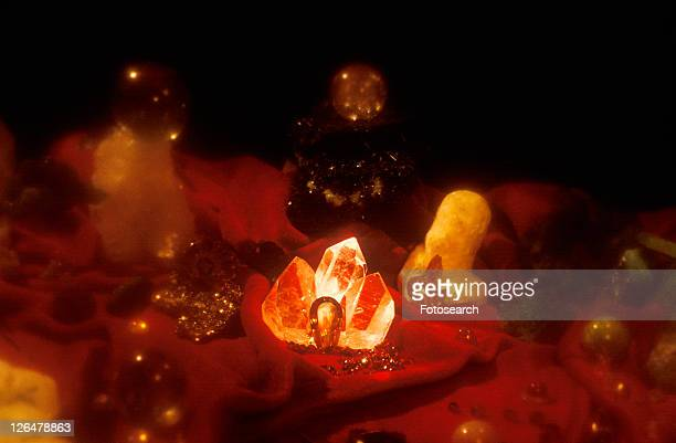 An assortment of precious jewels and glowing crystal rock formations on a ruby red cloth