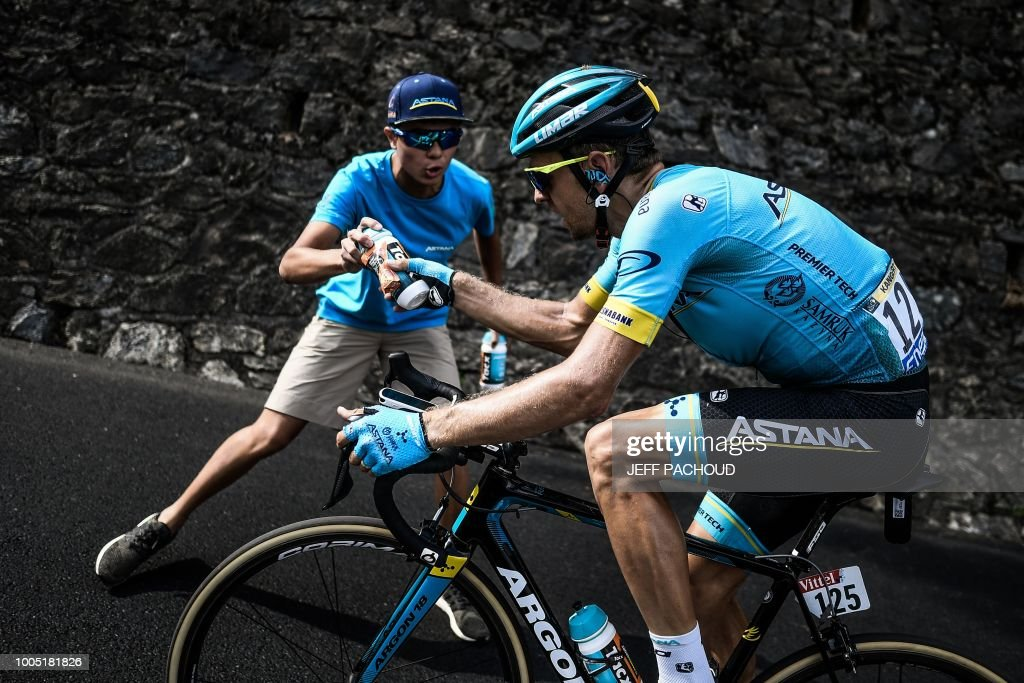 TOPSHOT - An Astana staff hands a water bottle to Estonia's Tanel Kangert as he ride during his breakaway in the 17th stage of the 105th edition of the Tour de France cycling race, between Bagneres-de-Luchon and Saint-Lary-Soulan Col du Portet, southwestern France, on July 25, 2018.