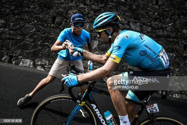 TOPSHOT An Astana staff hands a water bottle to Estonia's Tanel Kangert as he ride during his breakaway in the 17th stage of the 105th edition of the...