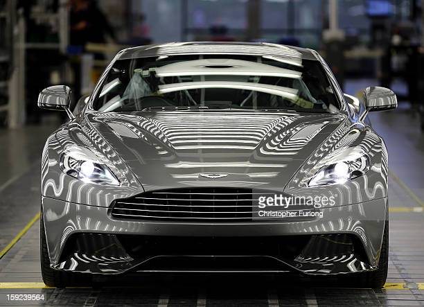 An Aston Martin Vanquish is inspected by hand inside a light booth at the company headquarters and production plant on January 10 2013 in Gaydon...