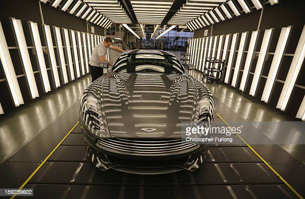 An Aston Martin Vanquish is inspected by hand inside a light booth by technician Matthew Goss at the company headquarters and production plant on...