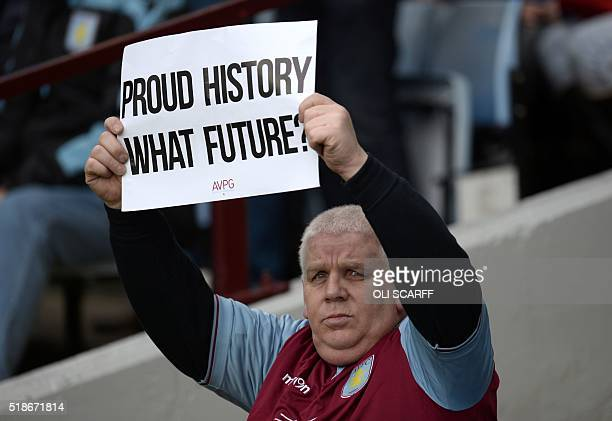 An Aston Villa fan holds a sign questioning his teams performances during the English Premier League football match between Aston Villa and Chelsea...