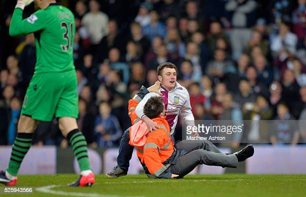 an Aston Villa steward wrestles an Aston Villa fan to the floor as fans invade the pitch after the second goal during the match