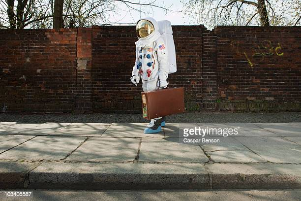 an astronaut carrying a suitcase and walking on a city sidewalk - astronaut stock-fotos und bilder