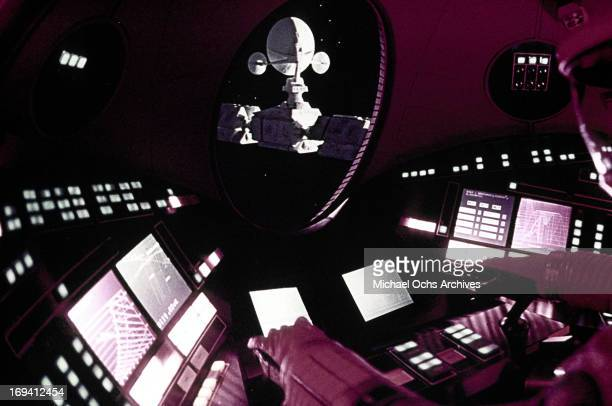 An astronaut controls the station while looking out the window in a scene from the film '2001 A Space Odyssey' 1968