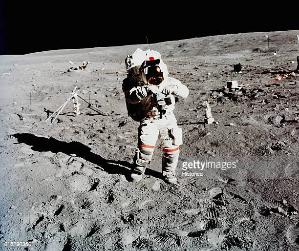 An astronaut from the Apollo 16 lunar landing mission on the Moon with various equipment for experiments April 1972 | Location Moon
