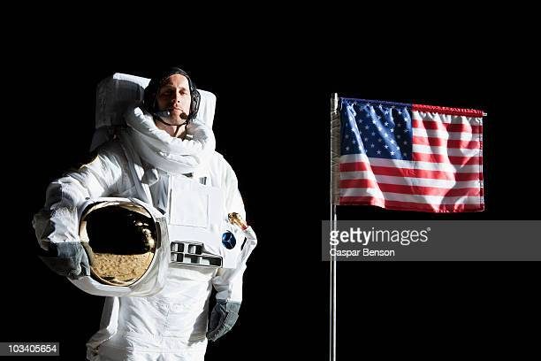 An astronaut holding his helmet standing next to an American flag, portrait