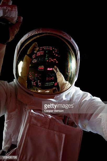 an astronaut in space making adjustments to a control panel - space helmet stock photos and pictures