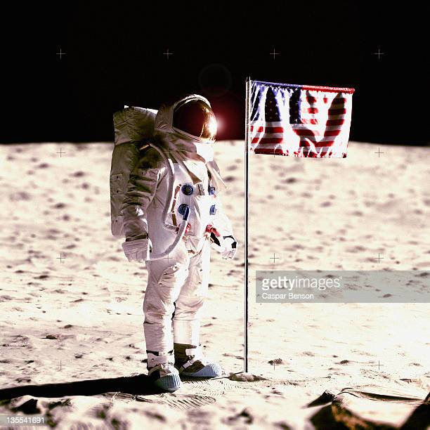 an astronaut next to an american flag on the moon - astronauta fotografías e imágenes de stock