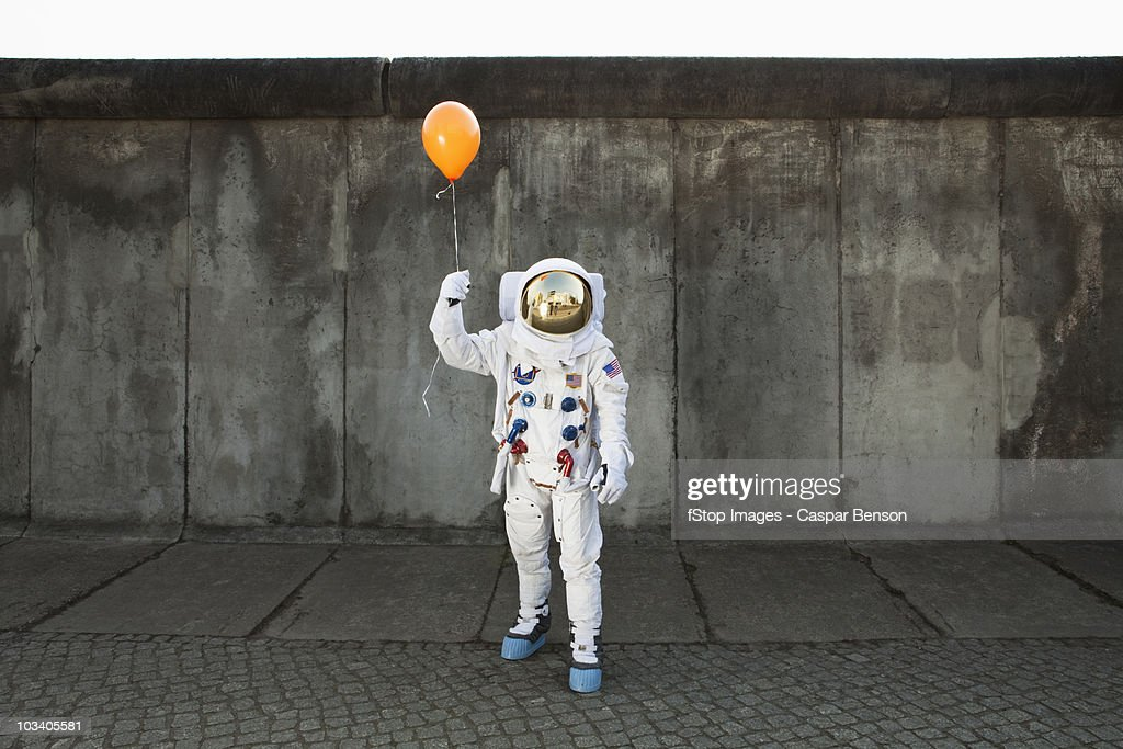 An astronaut on a city sidewalk holding a balloon : Photo