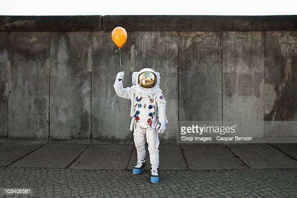 an astronaut on a city sidewalk holding a balloon - astronaut stock-fotos und bilder