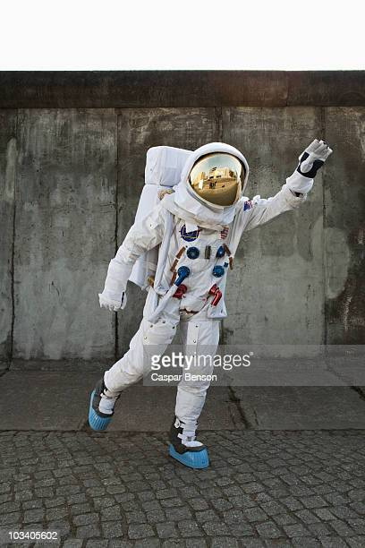 an astronaut on a city sidewalk pretending to take off in flight - astronauta fotografías e imágenes de stock