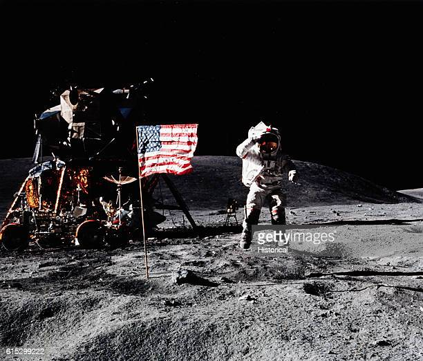 An astronaut on the Moon from the Apollo 16 lunar landing mission salutes the American flag as he jumps into the air April 1972 | Location Moon