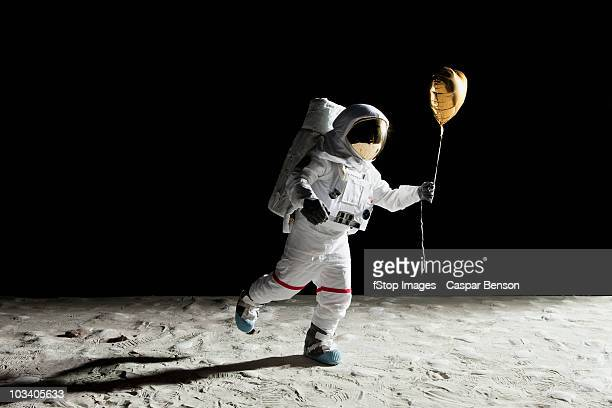 an astronaut on the moon holding a heart shaped helium balloon - astronaut stock-fotos und bilder