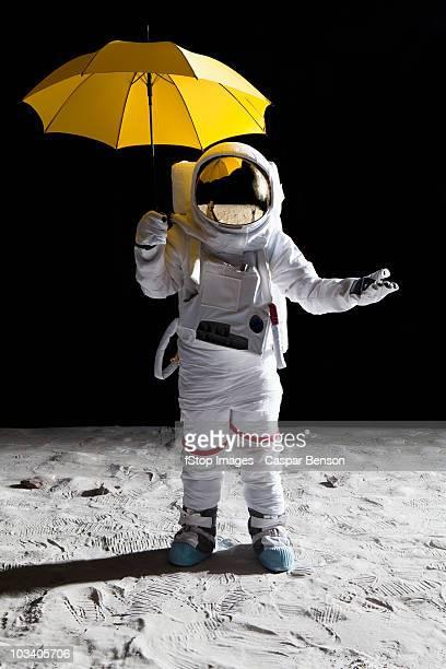 An astronaut on the moon holding an umbrella