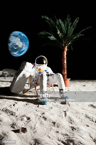 an astronaut on the moon relaxing in a beach chair - zurücklehnen stock-fotos und bilder