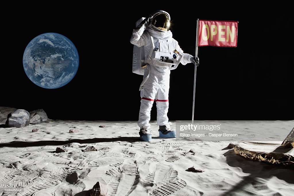 An astronaut on the moon saluting next to a flag with OPEN on it : Stock Photo