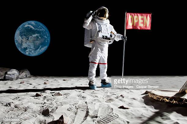 an astronaut on the moon saluting next to a flag with open on it - saluting stock pictures, royalty-free photos & images