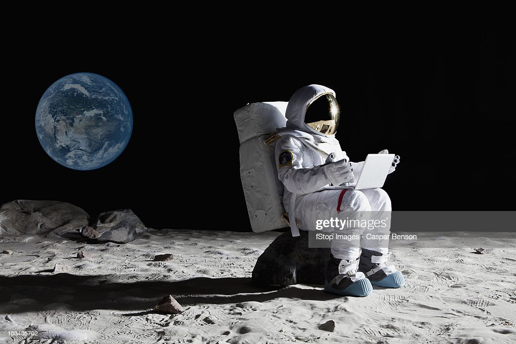An astronaut on the moon sitting on a rock using a laptop : Stock Photo
